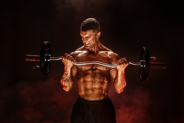 Hardy man doet oefening met zware balk Premium Foto