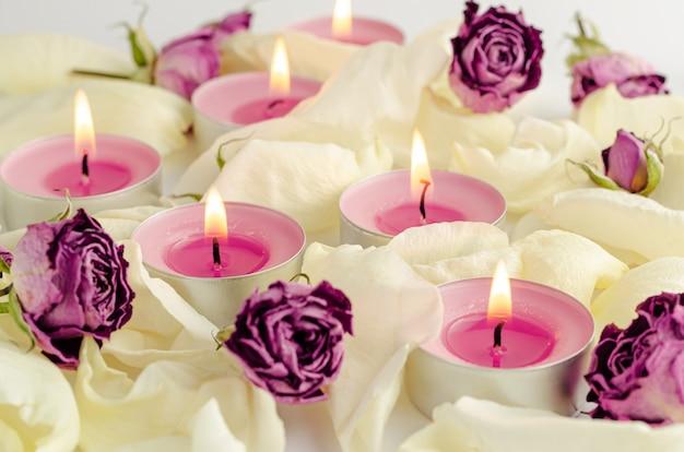 Harmonie en aromatherapie concept. brandende aromakaarsen, droge rozen en bloemblaadjesachtergrond. Premium Foto