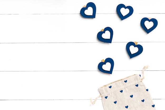 Hart en tas op witte houten oppervlak. valentijnsdag concept. trendy kleur Premium Foto