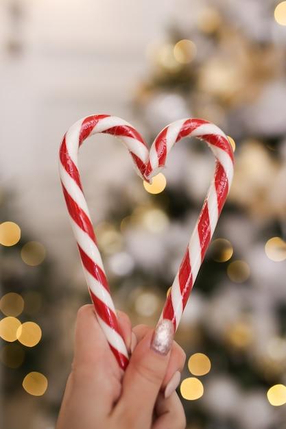 Hart gemaakt van kerst candy canes op een achtergrond van bokeh en slingers Premium Foto