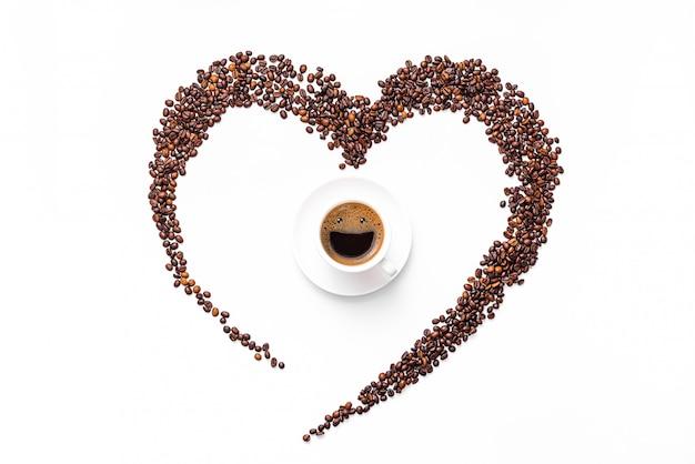 Hart gemaakt van koffiebonen en gemalen koffie op een witte ondergrond. in het midden is een kopje, in een kopje koffie schuim een blij lachend gezicht. verkwikkend drankje concept Premium Foto