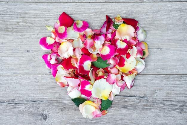 Hart gemaakt van roze bloemen op houten achtergrond voor valentijnsdag. Premium Foto
