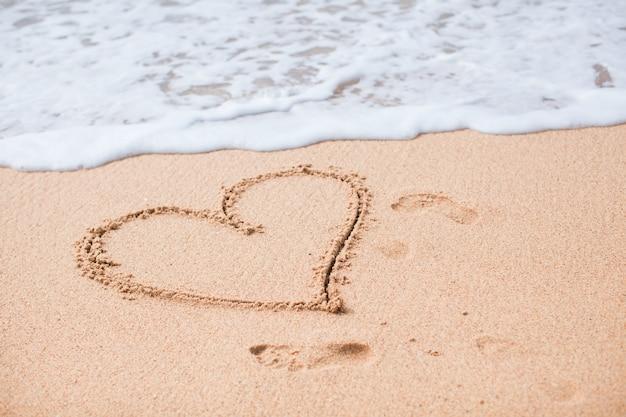 Hart geschilderd in het zand op een tropisch strand Premium Foto