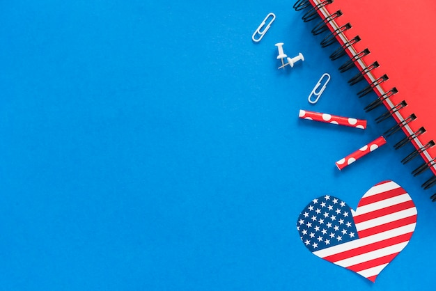 Hart in amerikaanse vlagkleur en kantoorbehoeften op blauwe oppervlakte Gratis Foto