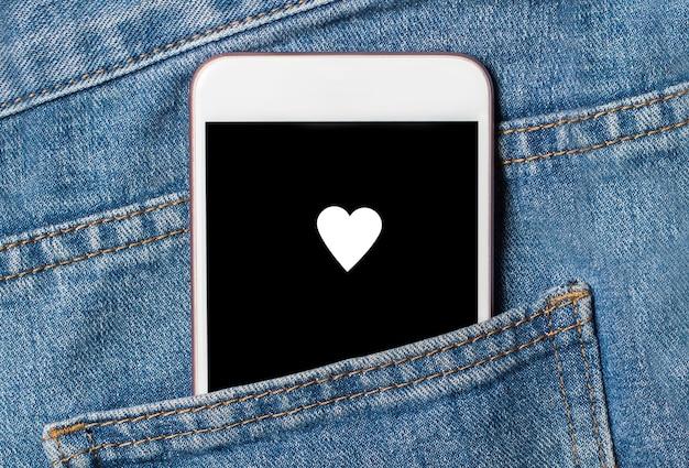 Hart op achtergrondtelefoon op jeansliefde en valentijnskaartconcept Premium Foto