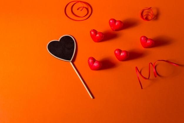 Harten van de de dag de romantische abstracte satijn van valentine en lintachtergrond. rode oranje achtergrond met harten Premium Foto