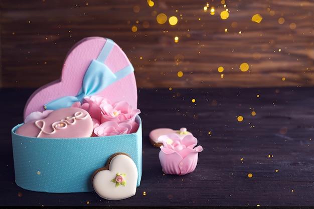 Hartenkoekjes in hart blauwe doos met rose op donkere houten achtergrond, exemplaarruimte Premium Foto