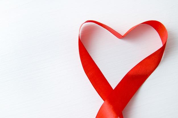Hartvorm gemaakt van rood lint op witte houten achtergrond Premium Foto