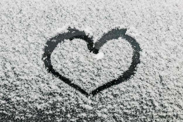 Hartvorm op sneeuwglas tijdens de winterdag Gratis Foto