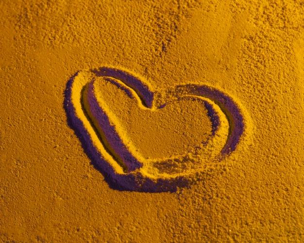 Hartvorm op zandtextuur die wordt getrokken Gratis Foto