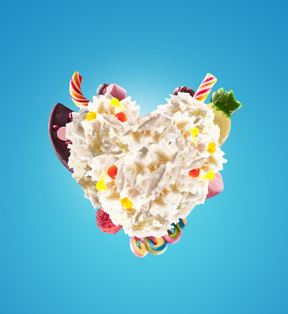 Hartvorm van slagroom met snoep, gelei, hart vooraanzicht. crazy freakshake food trend. geleverd hart van room, vol met bessen- en jelly-snoepjes, chocoladesuikergoedconcept. Premium Foto