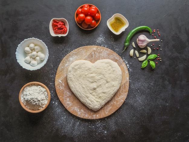 Hartvormig deeg en een aantal ingrediënten voor pizza op een zwarte tafel. het uitzicht vanaf de top Premium Foto