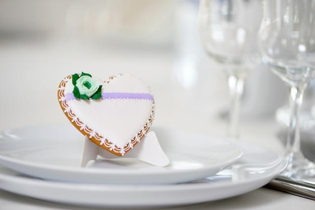 Hartvormig geglazuurd koekje - versierd met groene glazuurbloem en minuscule patroon staat op een wit bord als decoratie voor een feestelijke bruiloftstafel bij de wijnglazen Gratis Foto