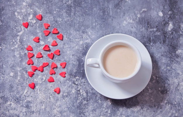 Hartvormig rood snoep en een kopje koffie op een concrete achtergrond Premium Foto