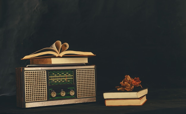 Hartvormige boeken geplaatst op retro-radio-ontvangers met gedroogde bloemen erop Gratis Foto