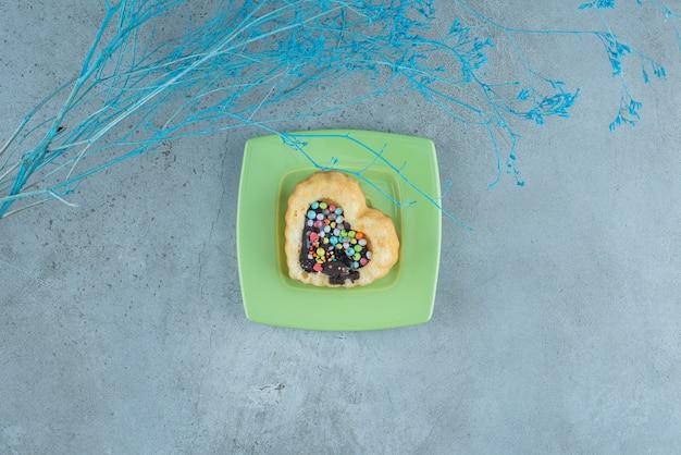 Hartvormige cake met chocolade en snoep vulling op een schotel op marmeren achtergrond. hoge kwaliteit foto Gratis Foto