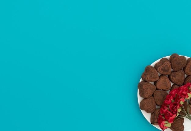 Hartvormige chocolade in witte kom op blauwe achtergrond met rode bloemen. Premium Foto