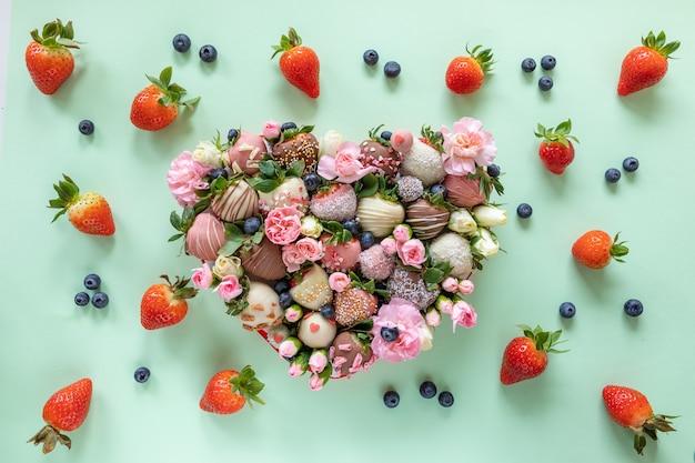 Hartvormige doos met handgemaakte chocolade bedekt aardbeien met verschillende toppings en bloemen als een geschenk op valentijnsdag op groene achtergrond Premium Foto