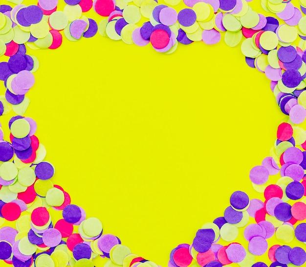 Hartvormige kleurrijke confetti op gele achtergrond Gratis Foto