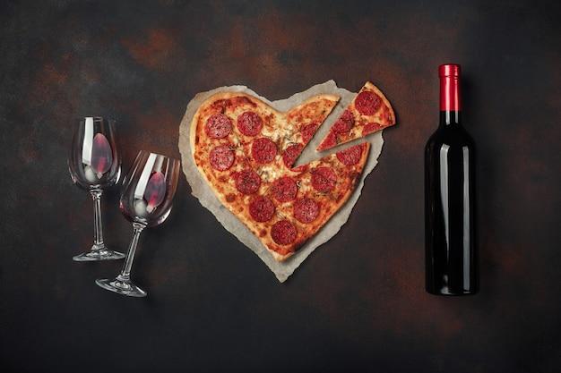 Hartvormige pizza met mozzarella, worst, wijnfles en twee wijnglas. de groetkaart van de valentijnskaartendag op roestige achtergrond. Premium Foto