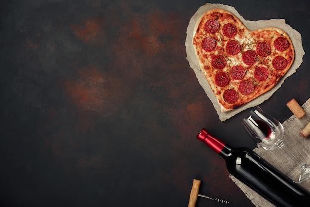 Hartvormige pizza met mozzarella, worstjes met een fles wijn en wijnglas. de groetkaart van de valentijnskaartendag op roestige achtergrond Premium Foto