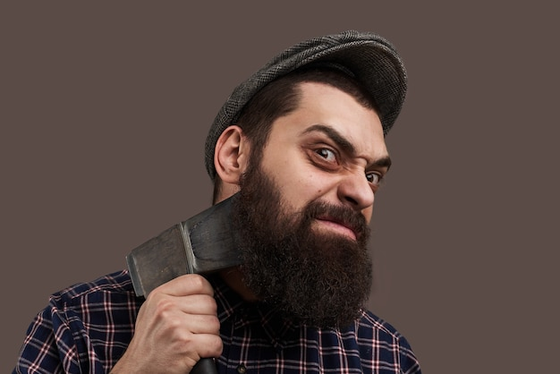 Hatelijk brute bebaarde man scheren door bijl. portret van hipster met baard. opvallend mannelijk concept. gekke emotie op het gezicht. Gratis Foto