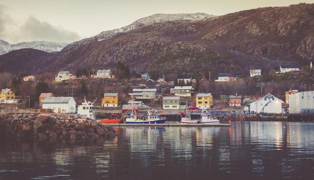 Haven in een klein vissersdorpje met afgemeerde boten en jachten met besneeuwde toppen op de achtergrond. Premium Foto