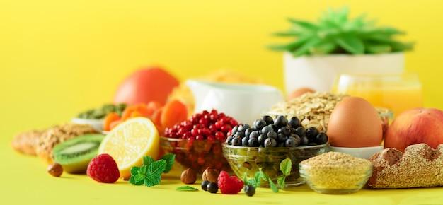 Haver en cornflakes, eieren, noten, fruit, bessen, toast, melk, yoghurt, sinaasappel, banaan, perzik Premium Foto