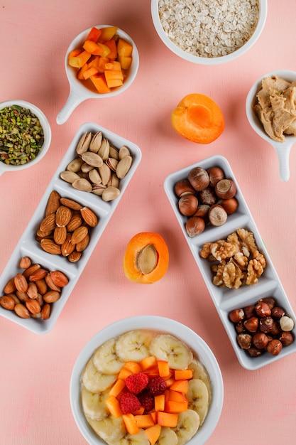 Havermout in een kom met fruit, noten, pindakaas, havervlokken Gratis Foto
