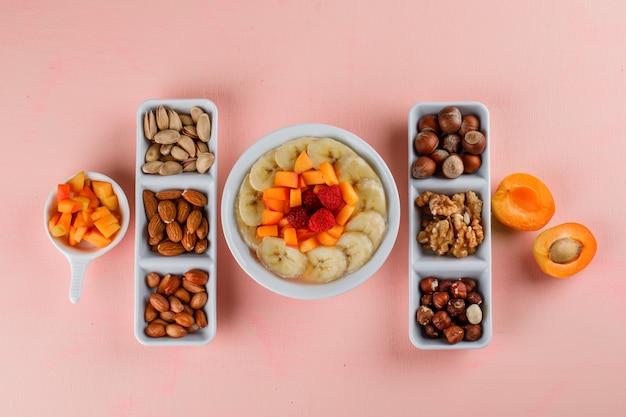 Havermout met banaan, abrikoos, bessen, noten in een kom Gratis Foto