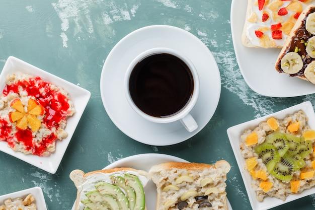 Havermout met fruit, jam, sandwich, koffie in platen Gratis Foto