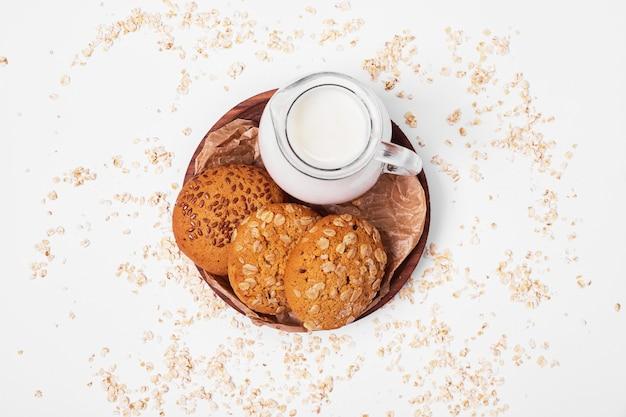 Havermoutkoekjes met melk op wit. Gratis Foto