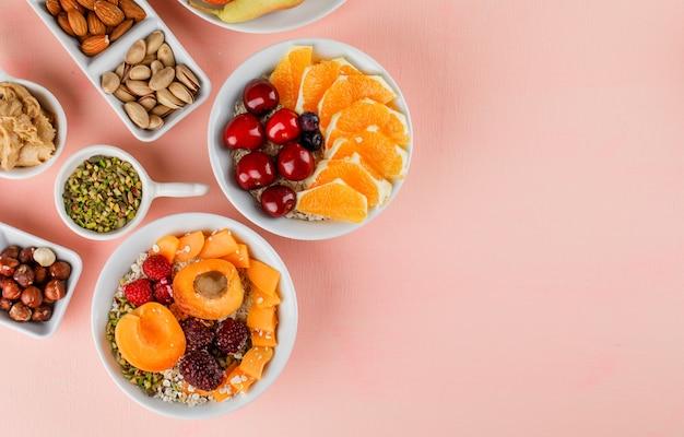 Havervlokken in kommen met fruit, noten, pindakaas Gratis Foto