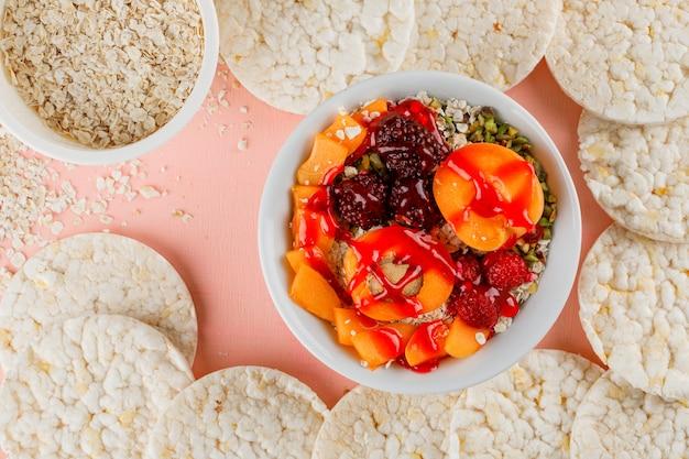 Havervlokken in kommen met noten, bessen, abrikoos, gelei, rijstwafels Gratis Foto