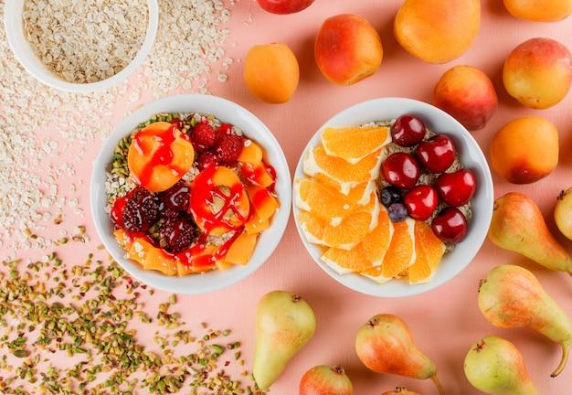 Havervlokken met noten, kersen, sinaasappel, bessen, peer, abrikoos in kommen Gratis Foto