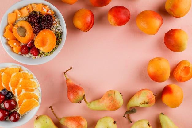 Havervlokken met pistache, abrikoos, bessen, peer, kers, sinaasappel in kommen Gratis Foto