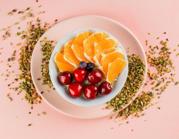 Havervlokken met pistache, kers, sinaasappel, bessen, plaat in een kom Gratis Foto
