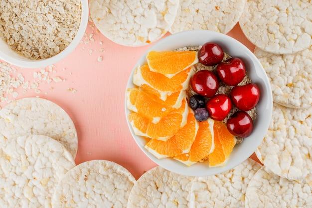 Havervlokken met sinaasappel, bessen, kersen, rijstwafels in kom Gratis Foto