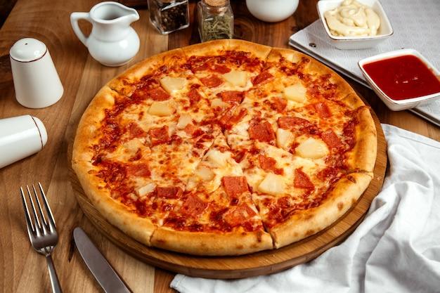 Hawaiiaanse pizza met gekookte ham, pizzasaus, kaas en ananas Gratis Foto