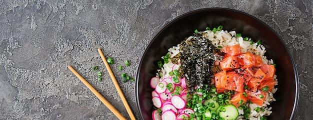 Hawaiiaanse zalm fish poke bowl met rijst, radijs, komkommer, tomaat, sesamzaad en zeewier. boeddha schaal. diëet voeding. bovenaanzicht. plat liggen. Gratis Foto
