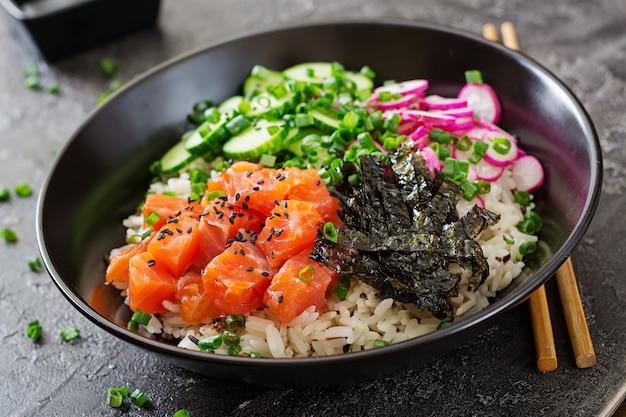 Hawaiiaanse zalm fish poke bowl met rijst, radijs, komkommer, tomaat, sesamzaad en zeewier. boeddha schaal. diëet voeding Gratis Foto