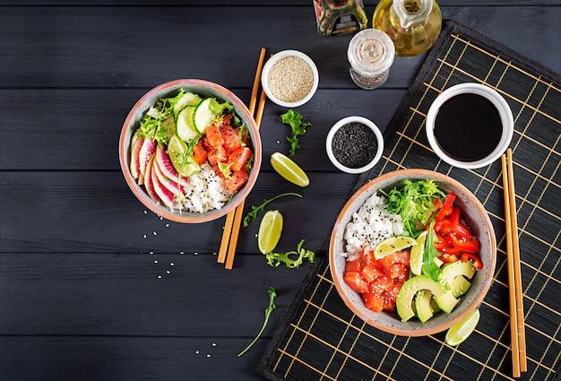 Hawaiiaanse zalmvissen porkom met rijst, avocado, paprika, komkommer, radijs, sesamzaad en limoen. Premium Foto