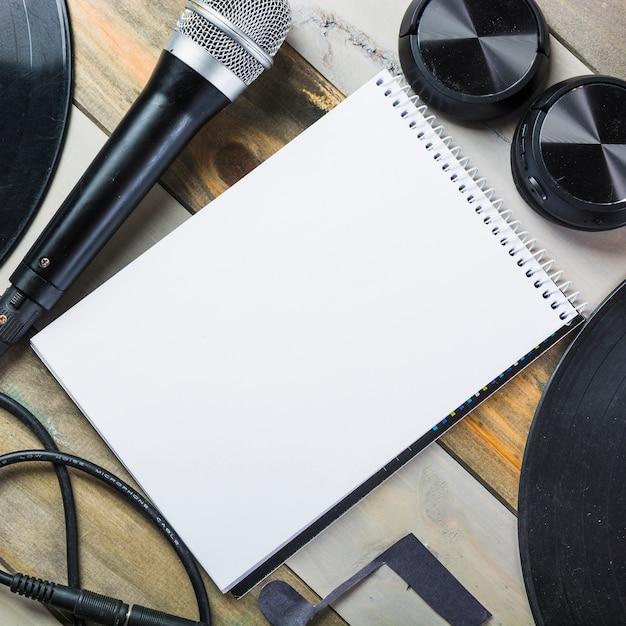 Headphone; microfoon; vinyl record en lege spiraal kladblok op houten tafel Gratis Foto