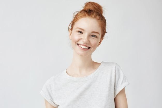 Headshot portret van gelukkige gembervrouw met sproeten die wit glimlachen. Gratis Foto