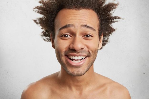 Headshot van aangenaam uitziende mannelijke man met ruige kapsel, borstelharen, glimlacht gelukkig, Gratis Foto