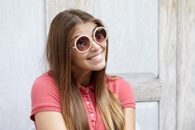 Headshot van flirterige jonge vrouw die modieuze tinten draagt met een speelse look en een schattige verlegen glimlach terwijl ze tegen een houten muur poseren met kopie ruimte voor uw informatie of advertentie Gratis Foto