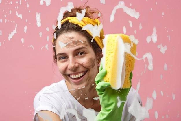 Headshot van gelukkig mooie positieve jonge huisvrouw met charmante glimlach raam in de keuken wassen, dik schuim van glazen oppervlak wegvegen, genieten van reinigingsproces, glimlachend Gratis Foto