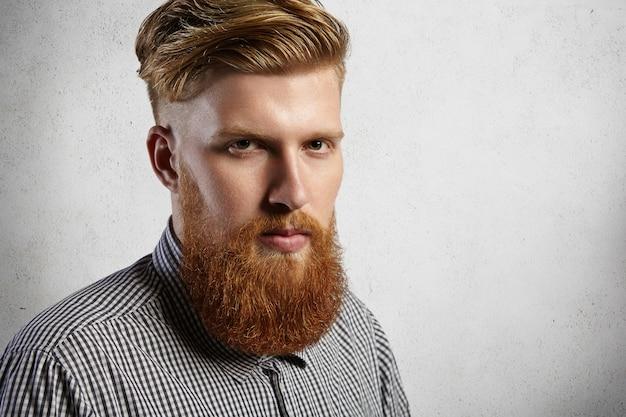Headshot van knappe en stijlvolle blanke man gekleed in een geruit overhemd. brute en zelfverzekerde hipster met dikke baard en goed getrimde snorren. Gratis Foto