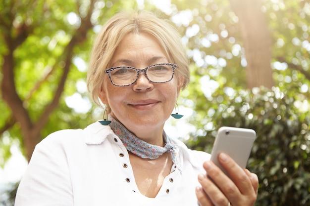 Headshot van mooie blanke vrouwelijke gepensioneerde op zoek met vrolijke, vrolijke uitdrukking terwijl ze mobiele telefoon gebruikt om online te communiceren met haar vrienden, nieuws te lezen, foto's te verzenden Gratis Foto