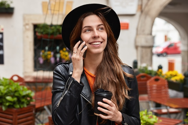 Headshot van mooie vrolijke vrouw blij om oude vriend via mobiele telefoon te horen, heeft reis naar het buitenland Gratis Foto